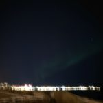 Green banded Aurora with reykjavik in background